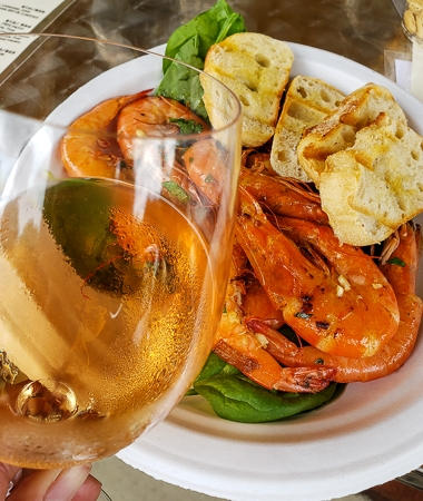 Wine with shrimp and crostini on plate